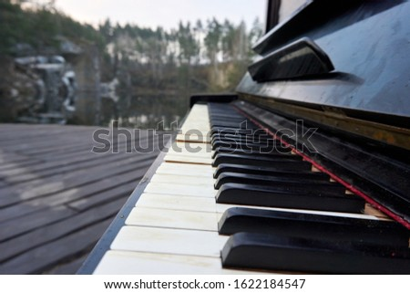 Close up shot of the old piano keyboard. Some keyboard are broken. The piano are black and keyboards have damage. #1622184547