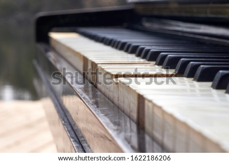Close up shot of the old piano keyboard. Some keyboard are broken. The piano are black and keyboards have damage. #1622186206