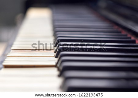 Close up shot of the old piano keyboard. Some keyboard are broken. The piano are black and keyboards have damage. #1622193475