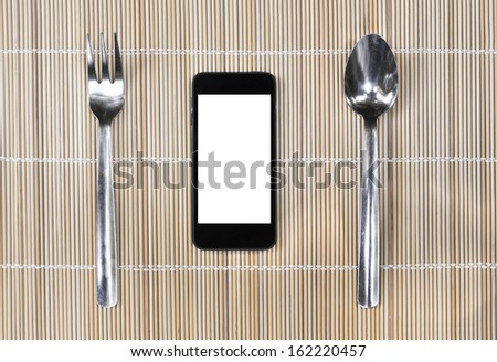 Smartphone with fork and spoon on bamboo mat background, eating and planning