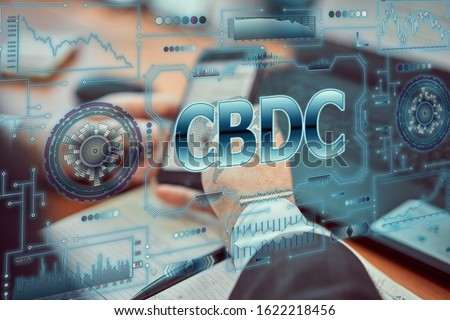 """A young businessman uses a futuristic smartphone with the latest holographic technology of augmented reality with the inscription """"CBDC"""". Central bank digital currency concept Royalty-Free Stock Photo #1622218456"""