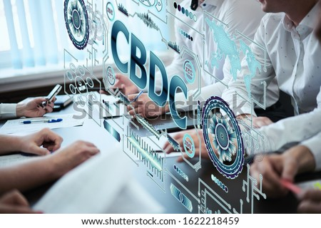 A group of young people discuss the concept of central bank digital currency. Holographic futuristic screen with the inscription CBDC Royalty-Free Stock Photo #1622218459