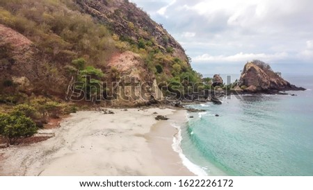 A view on an idyllic Koka Beach. Hidden gem of Flores, Indonesia. Steep slopes of the hills joining the sea. Waves gently washing the shore. There are hills in the back. Happiness and love #1622226172