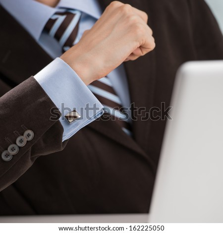 Closeup of torso of confident business man wearing elegant suit working with his laptop at office #162225050