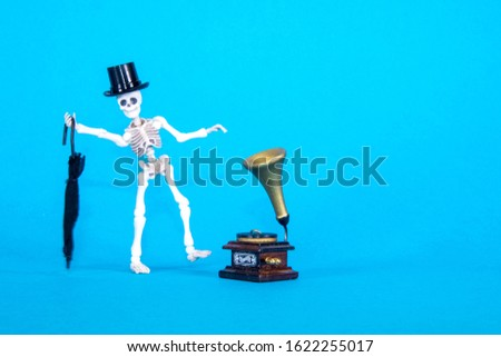 A plastic toy skeleton is happy and dancing to the music coming from the gramophone. #1622255017