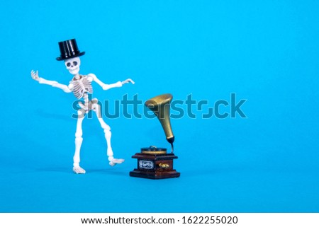 A plastic toy skeleton is happy and dancing to the music coming from the gramophone. #1622255020