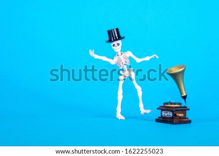 A plastic toy skeleton is happy and dancing to the music coming from the gramophone. #1622255023