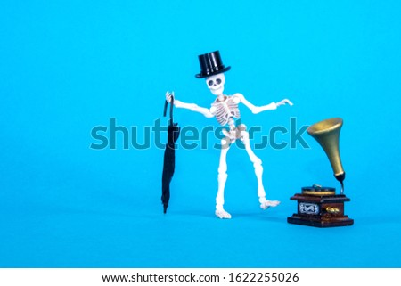 A plastic toy skeleton is happy and dancing to the music coming from the gramophone. #1622255026
