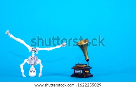 A plastic toy skeleton is happy and dancing to the music coming from the gramophone. #1622255029