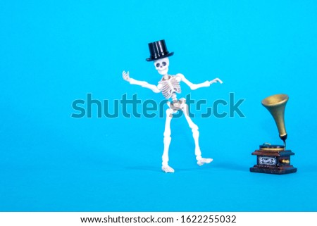 A plastic toy skeleton is happy and dancing to the music coming from the gramophone. #1622255032