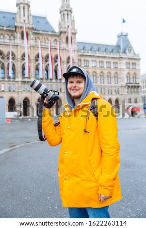 man in yellow raincoat with big dslr camera at city square