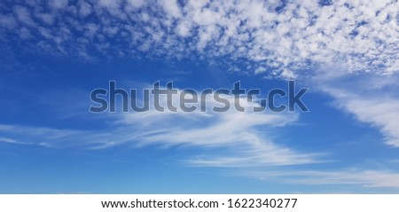 Small fluffy white clouds in blue sky in January. #1622340277