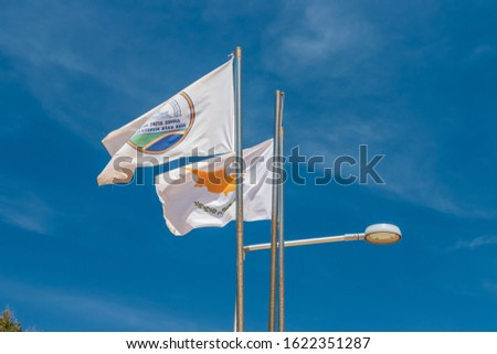 The flag of Agia Napa municipality and the flag of Cyprus. Flags on the flagpole and the stereet lamp post. The wind inflates the flag. #1622351287