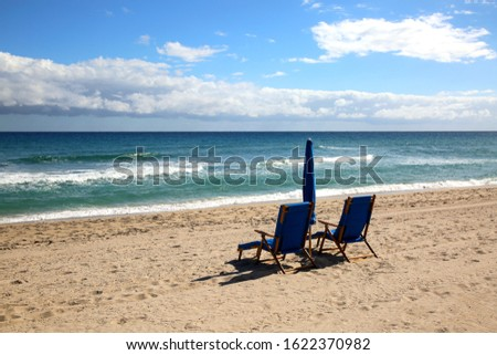 Empty beach with two lounge chairs and umbrella sunny day at Delray beach Florida   #1622370982