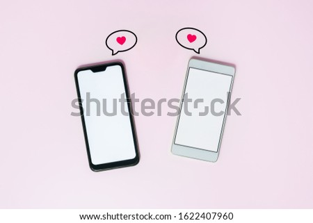 Two phones with white screens and messaging icons. Messaging, love texting and online dating concept. St. Valentine's day concept #1622407960