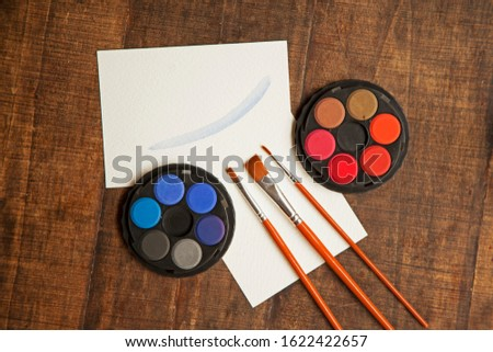 blank sheet on the table with paintbrushes and watercolor #1622422657