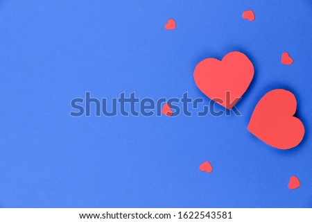 Blue background with red hearts. Valentine's day background. Two big red hearts and a few small ones on the right on a blue background. Close-up, free space on the left, horizontal. Concept of love.