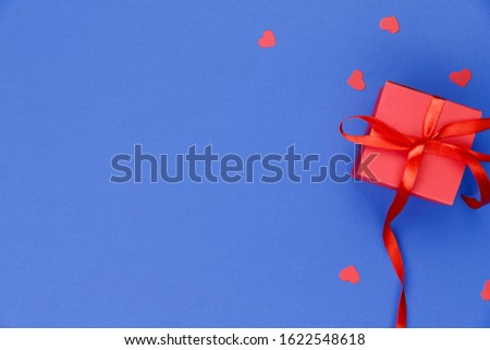 Blue background with red little hearts and a red box with a gift. Valentine's day background. On the right is a red gift box with a red ribbon. Close-up, free space on the left, horizontal. Flat lay
