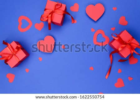 Valentine's day background. Blue background with red hearts and a red box with a gift. Red boxes with red ribbons on a blue background. Close-up, free space, horizontal. Love concept. Flat lay