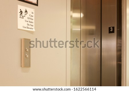 "Silver elevator door at an office building in Las Vegas, NV. Paper sign on wall says, ""in case of fire use stairs. Do not use elevator."""