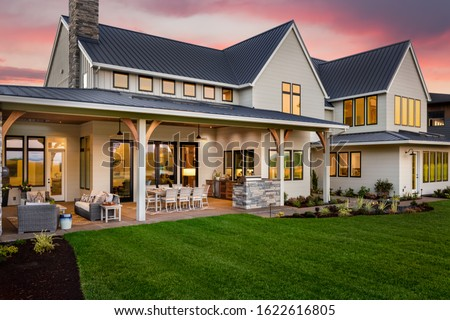 Beautiful luxury home exterior at sunset. Features large covered patio with outdoor furniture, barbecue, and table with chairs.