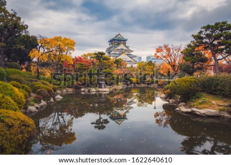 Osaka Castle building with colorful maple leaves or fall foliage in autumn season. Colorful trees, Kyoto City, Kansai, Japan. Architecture landscape background. Famous tourist attraction.