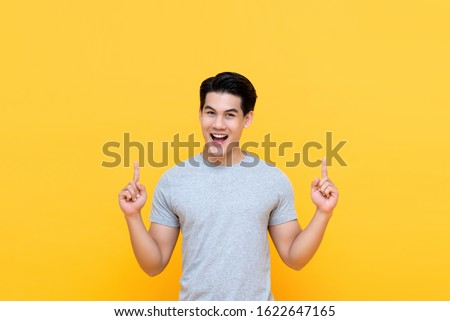 Happy handsome smiling young Asian man with hands poiting up to empty space above #1622647165