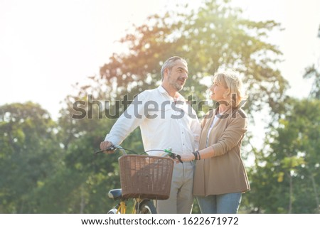 Cheerful active senior couple with bicycle walking through park together. Perfect activities for elderly people in retirement lifestyle. #1622671972