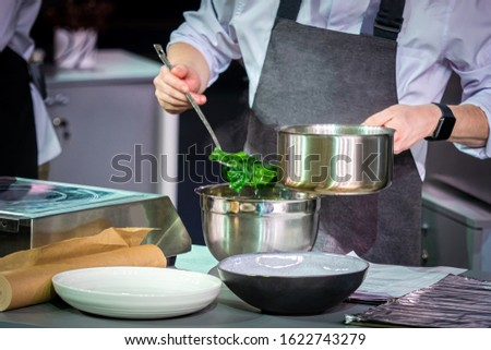 Cook pulls out green leaves. Preparation of decoction from plants. Herbal decoction. Cook takes out a slotted spoon grass. Recipes Vegetarians. Dishes from vegetables. Concept - refusal to eat meat #1622743279