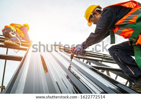 [Construction roof] Roofer worker in protective uniform wear and gloves, Construction worker install new roof,Roofing tools,Electric drill used on new roofs with Metal Sheet. #1622772514