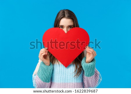 Someone is loved. Blushing cute and silly girlfriend want confess in love, deep feelings, hiding face behind big lovely red heart and looking camera, express affection standing over blue background #1622839687