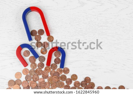 Magnets attracting coins on white wooden table, flat lay. Space for text #1622845960