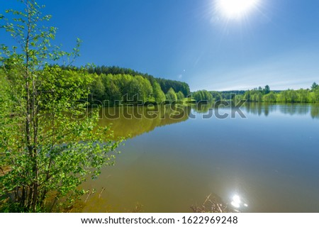 The lake is a large body of water surrounded by land. Walnut and pine trees grow along the edge, complete calm, beautiful hatching in the water #1622969248