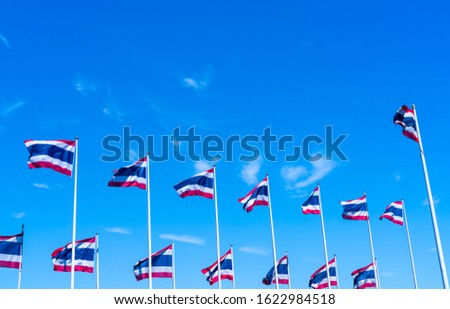 Many of Thailand flag waving on top of flagpole against blue sky. Thai flag was drawn to top of the flagpole. Red, blue, and white color rectangle fabric. National flag of the Kingdom of Thailand. #1622984518