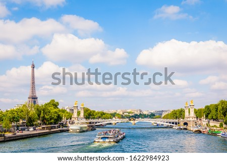 Cityscape of Paris, France, with a bateau-mouche cruising on the river Seine, the Alexandre III bridge, the Eiffel tower on the left and the Chaillot palace in the distance by a sunny summer day. #1622984923