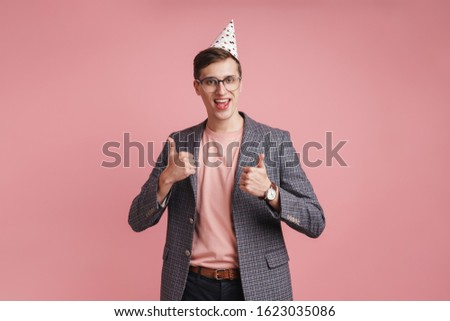 Image of a happy positive young boy in glasses in birthday cap isolated over pink wall background showing thumbs up.