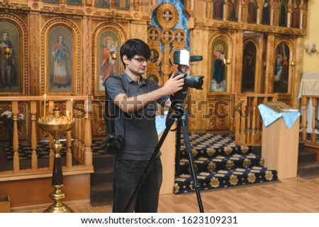 videographer working with camera and light at church