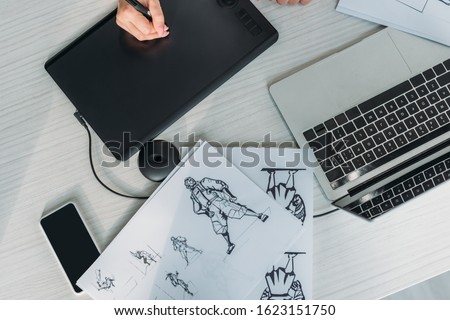 top view of animator using digital tablet near sketches