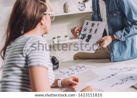 cropped view of illustrator holding cartoon sketches near woman #1623151810