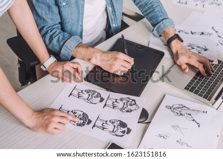cropped view of illustrator pointing with finger at cartoon sketch near coworker #1623151816