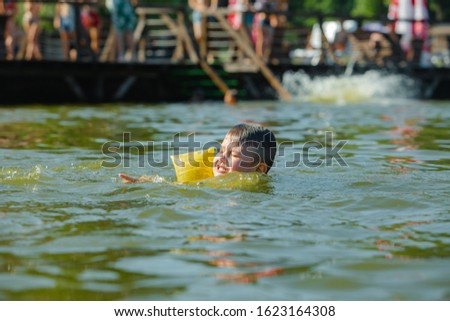 little toddler kid swimming in lake with inflatable arms aids support