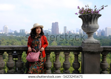 An Asian female touring posing for a picture on a balcony overlooking the Bosque de Chapultepec or Chapultepec Forest from Chapultepec Castle in Mexico City, Mexico.