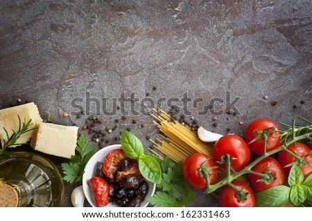 Italian food background, with vine tomatoes, basil, spaghetti, mushrooms, olives, parmesan, olive oil, garlic, peppercorns, rosemary, parsley and thyme.  Slate background. Royalty-Free Stock Photo #162331463
