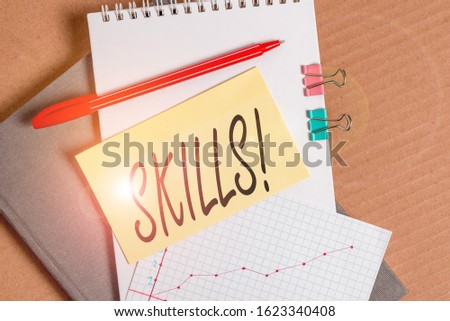 Word writing text Skills. Business concept for ability do something very well by nature Desk notebook paper office cardboard paperboard study supplies table chart. #1623340408