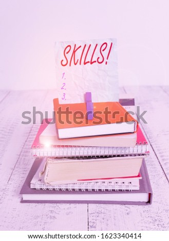 Conceptual hand writing showing Skills. Business photo showcasing ability do something very well by nature pile stacked books notebook pin color reminder white wooden. #1623340414