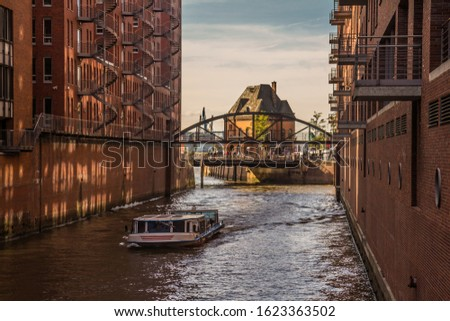Canal in Hamburg, Germany, bridge with tourists across it and touristic ferry