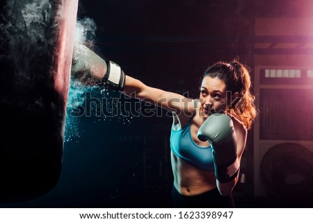 young woman training boxing in the punching bag - sport, self defense, boxing and training concepts - swing boxing Royalty-Free Stock Photo #1623398947