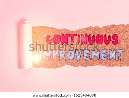 Handwriting text Continuous Improvement. Concept meaning ongoing effort to improve products or processes Cardboard which is torn in the middle placed above a wooden classic table. #1623404098