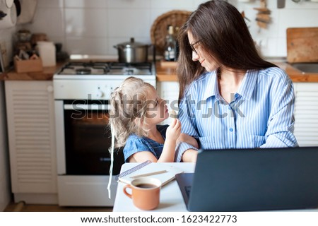 Working mom works from home office. Happy mother and daughter look to each other. Woman and cute child using laptop. Freelancer workplace in cozy kitchen. Female business, kindness, care. Lifestyle. #1623422773