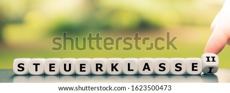 """Hand turns a dice and changes the German expression """"Steuerklasse I"""" (""""German tax class 1"""") to (""""Steuerklasse II"""" (""""German tax class 2""""), #1623500473"""